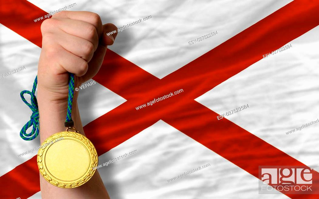 Photo de stock: Winner holding gold medal for sport and flag of us state of alabama.