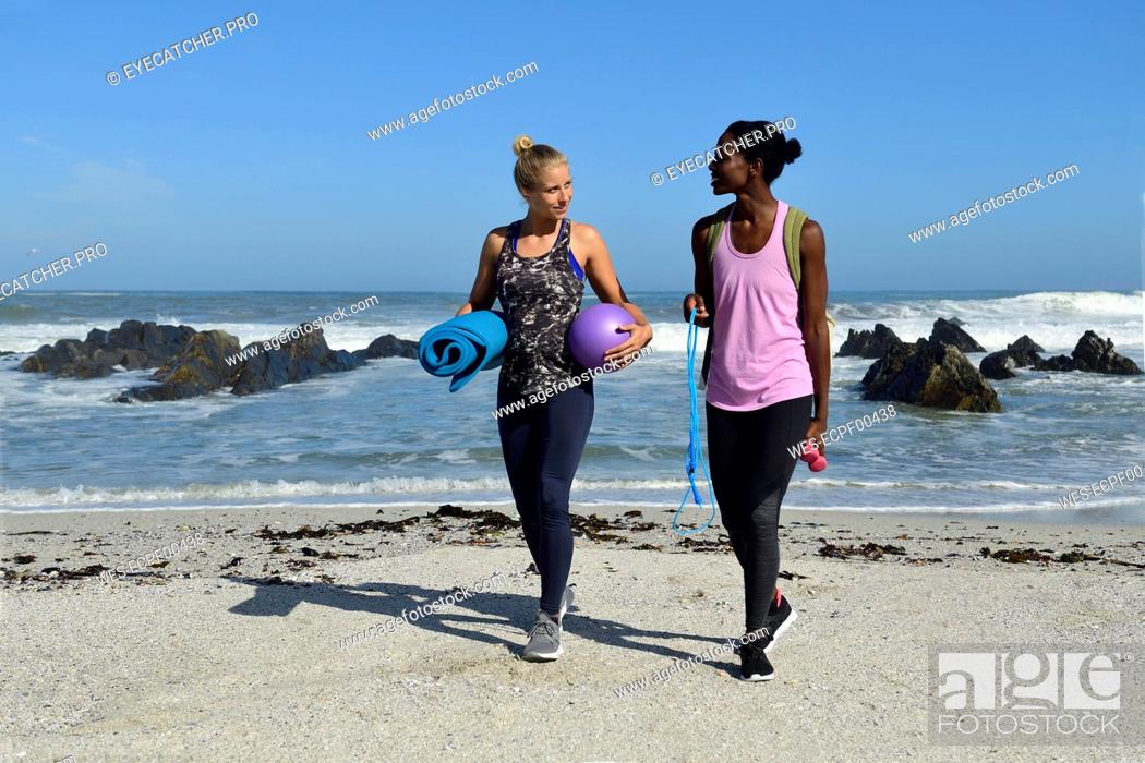 Stock Photo: Two women with fitness equipment walking on the beach.