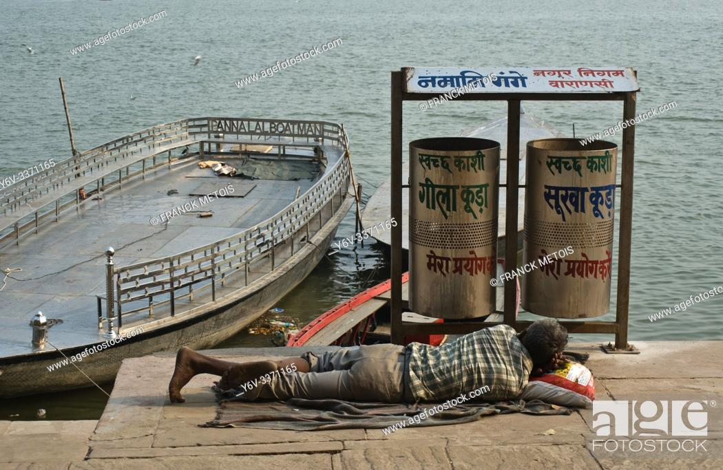 Stock Photo: Poor man sleeping near a public dustbin ( Varanasi, India). Ganges river in the background.