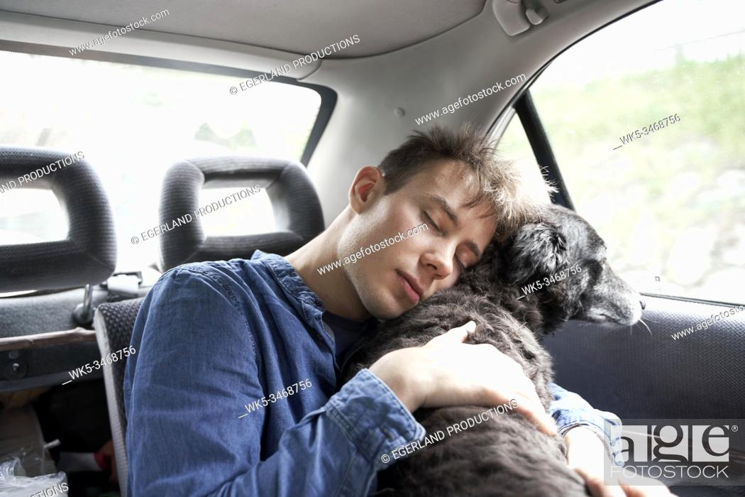 Stock Photo: Teen boy sitting in the backseat of the car with his dog.