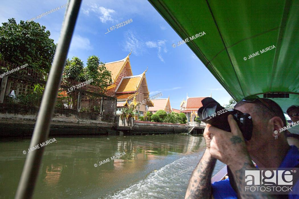 Stock Photo: A tourist photographs temples from a longboat on one of Bangkoks many canals, Thailand.