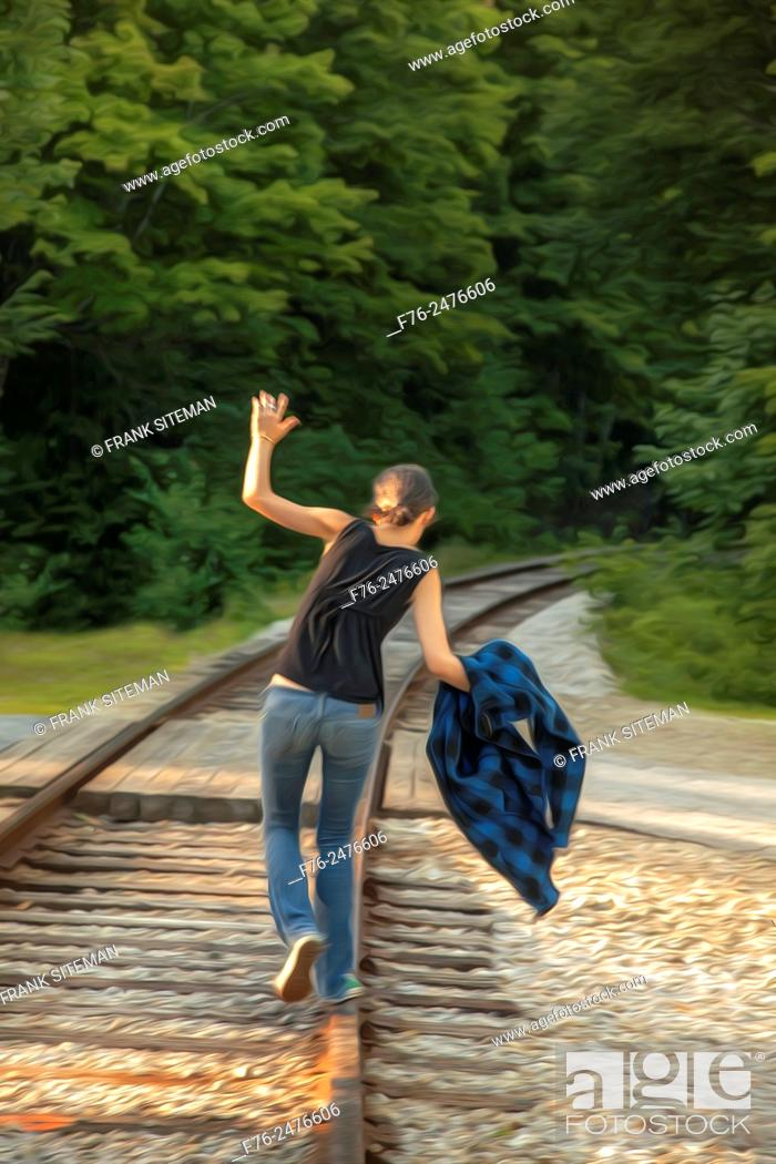 Stock Photo: Stylized image of girl in jeans balancing on / walking on railroad tracks in New Hampshire, USA.