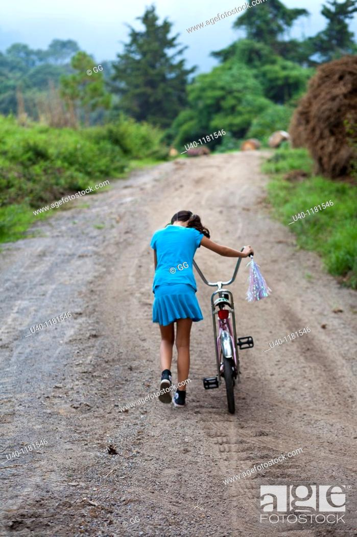 Stock Photo: Girl pushing bike up country road.