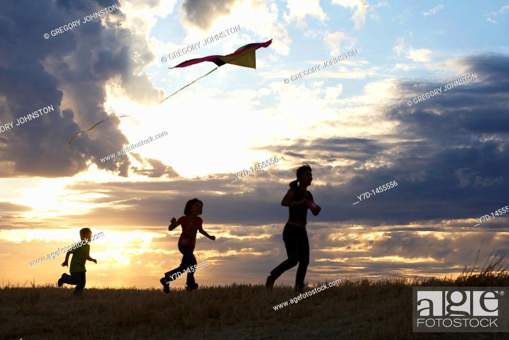 Stock Photo: A young boy aims for the sky with his kite.