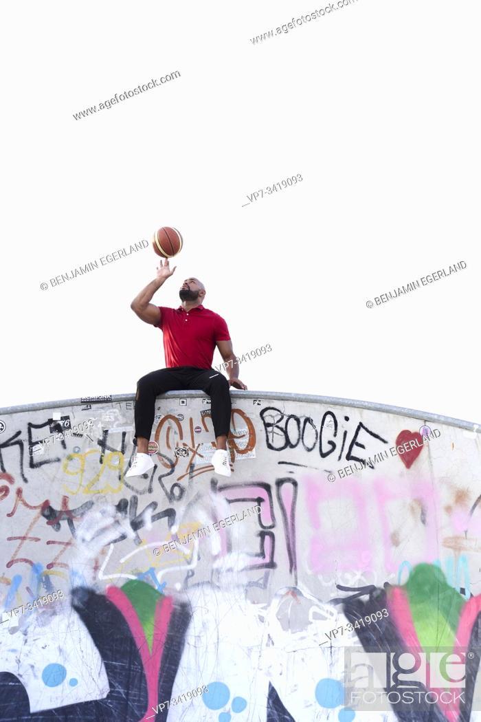 Stock Photo: Athletic man spinning basketball on fingers. Frankfurt, Germany.