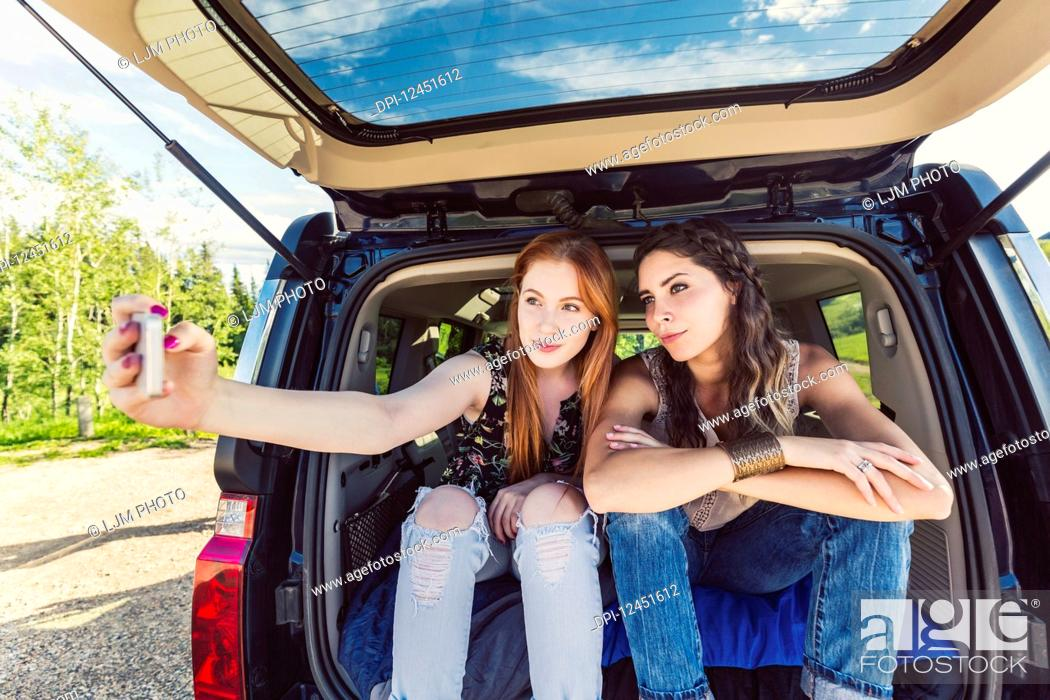 Stock Photo: Two young women on a road trip sit in the back of a vehicle taking a self-portrait with a smart phone; Edmonton, Alberta, Canada.