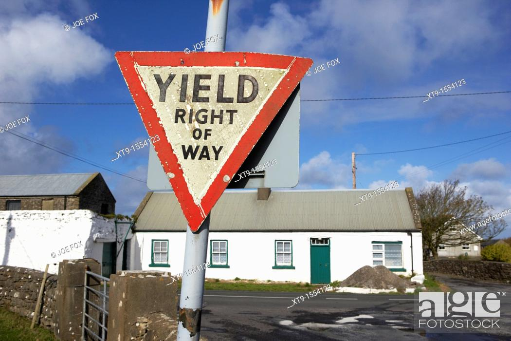 Stock Photo: old irish red triangle yield right of way sign in rural ireland.