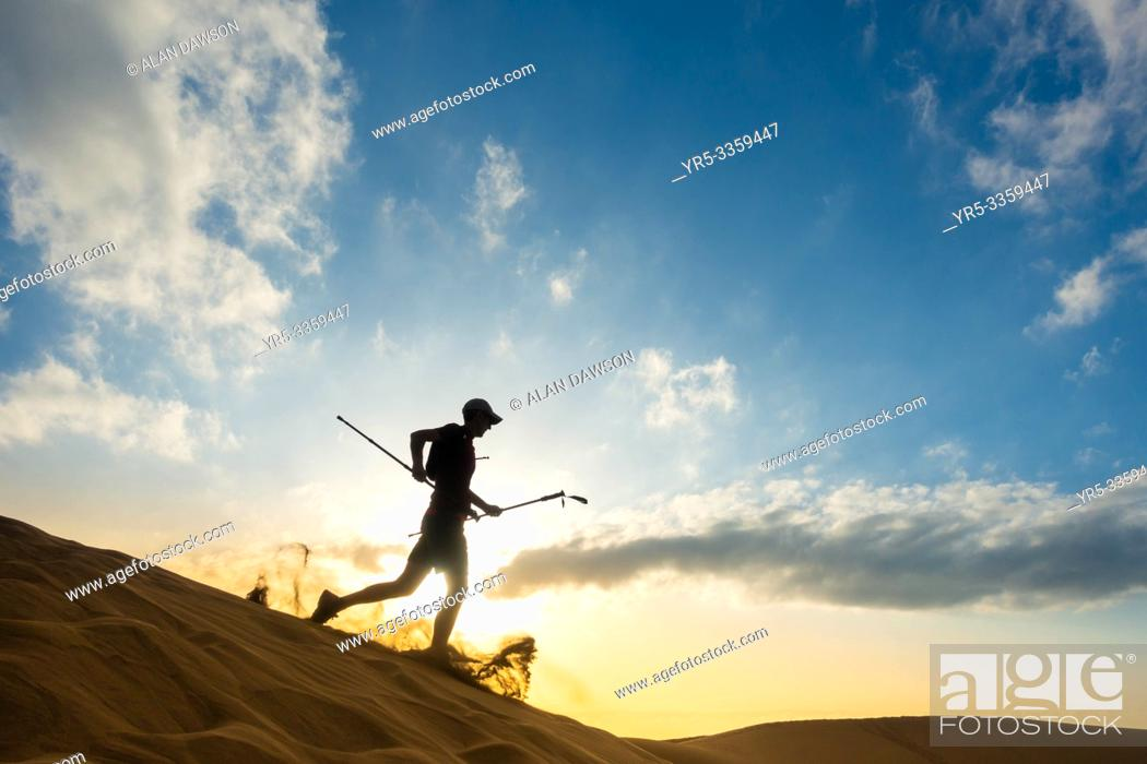 Stock Photo: 62 year old trail runner training on sand dunes at sunrise at Maspalomas, Gran Canaria, Canary Islands, Spain.