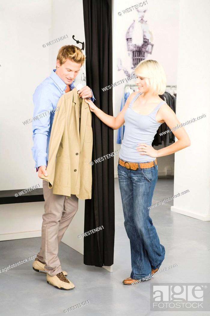 Stock Photo: Young couple in changing room, man holding jacket.