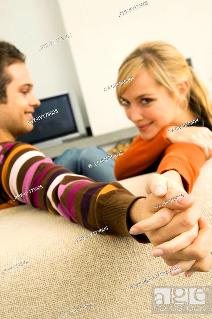 Stock Photo: Side profile of a young couple holding hands and smiling.
