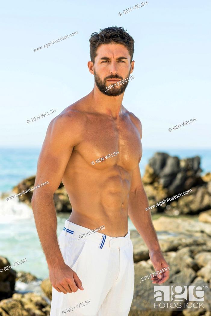 Stock Photo: Portrait of a shirtless man wearing white shorts on the rocky coast; Tarifa, Cadiz, Andalusia, Spain.