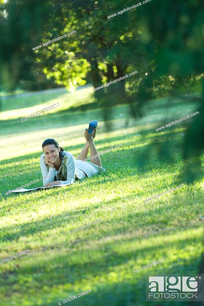 Stock Photo: Young woman lying on grass, smiling at camera.