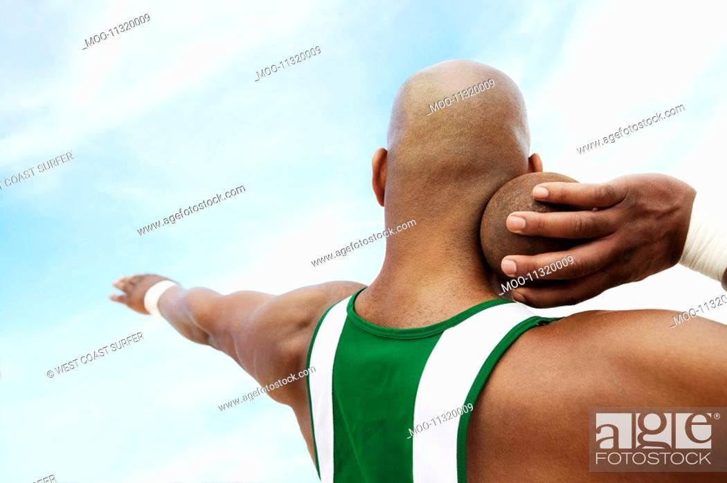 Stock Photo: Shot Putter holding shot put head and shoulders back view.