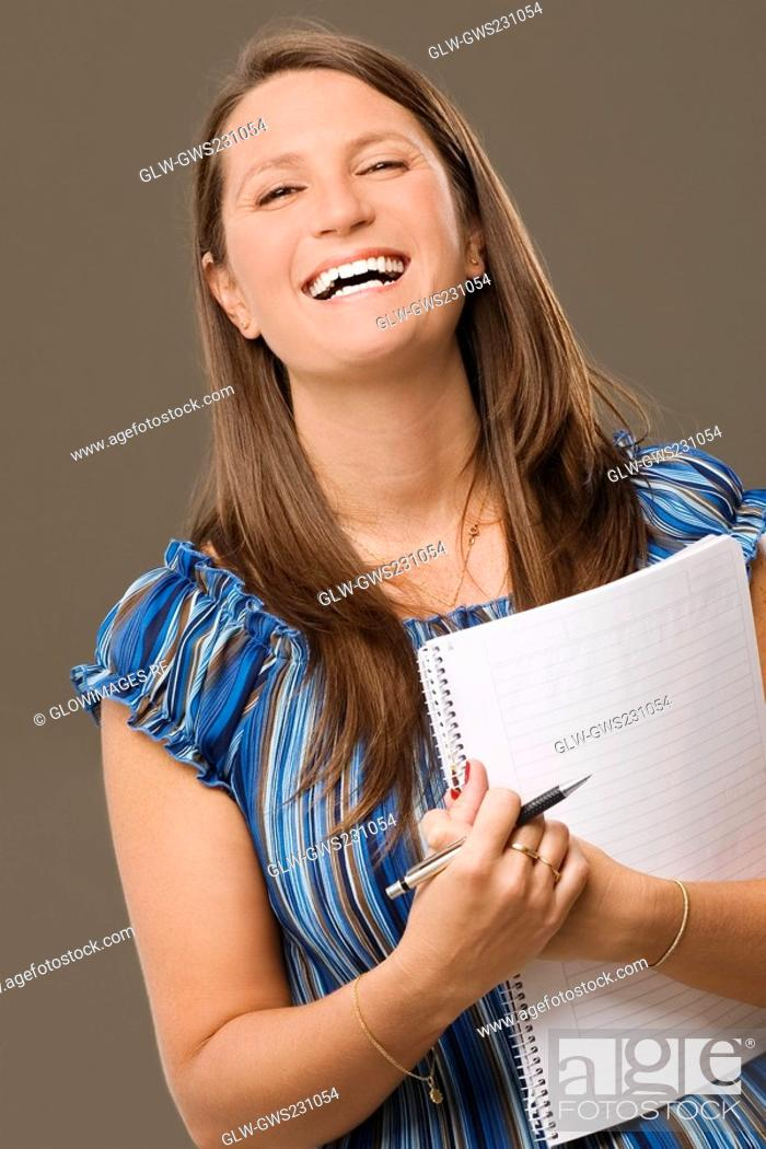 Stock Photo: Portrait of a mid adult woman holding a spiral notebook and smiling.