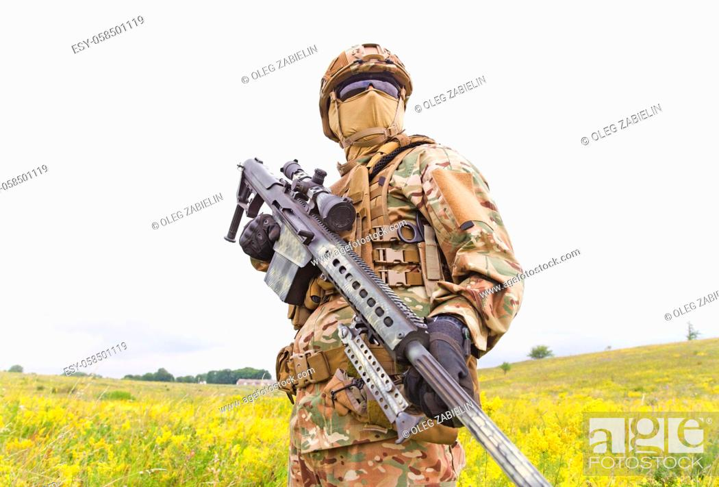 Imagen: Armed special forces soldier with sniper rifle stands in field.