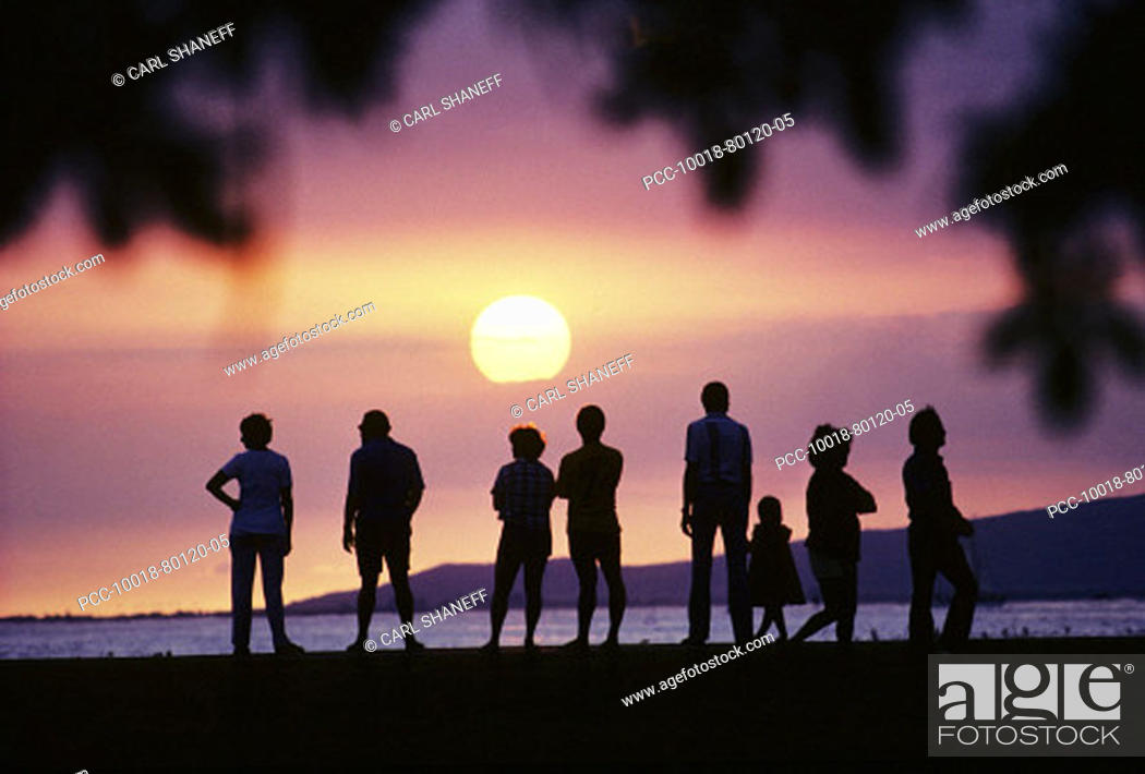 Stock Photo: Silhouette of a group of people standing on beach watching a gorgeous sunset.