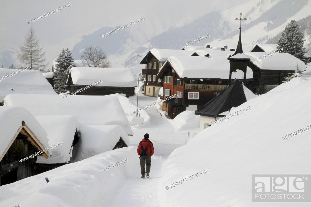 Stock Photo: Man strolling through snow covered village.