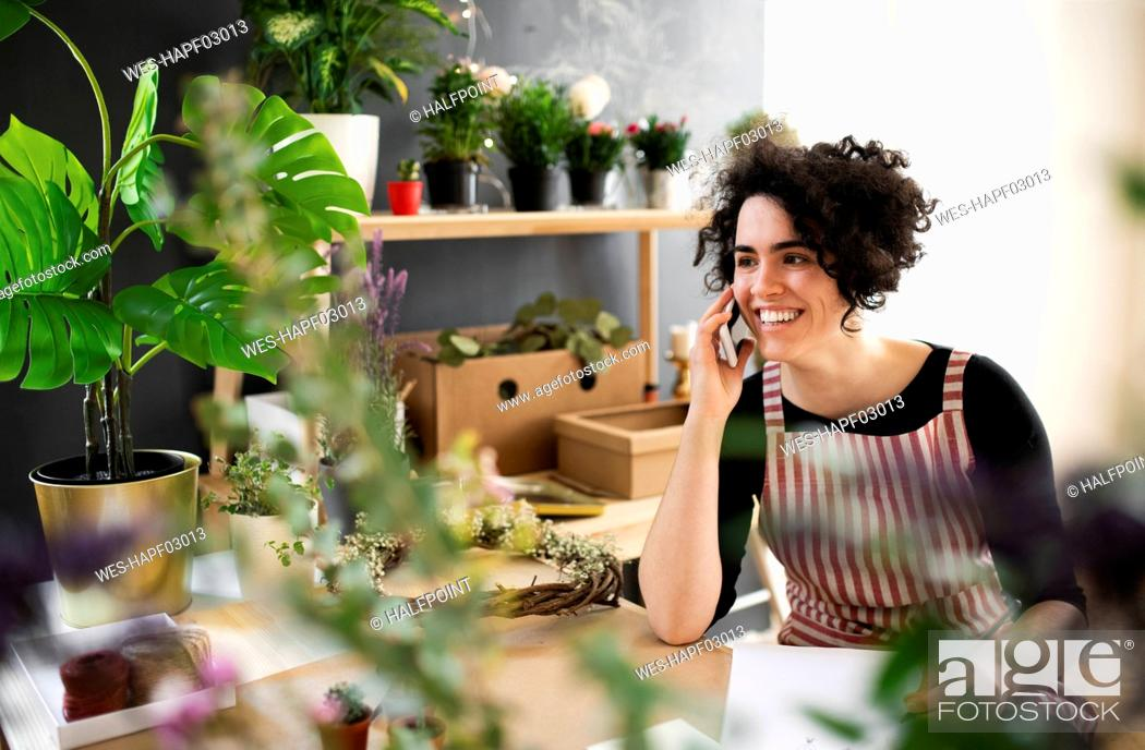 Stock Photo: Happy young woman on the phone in a small shop with plants.