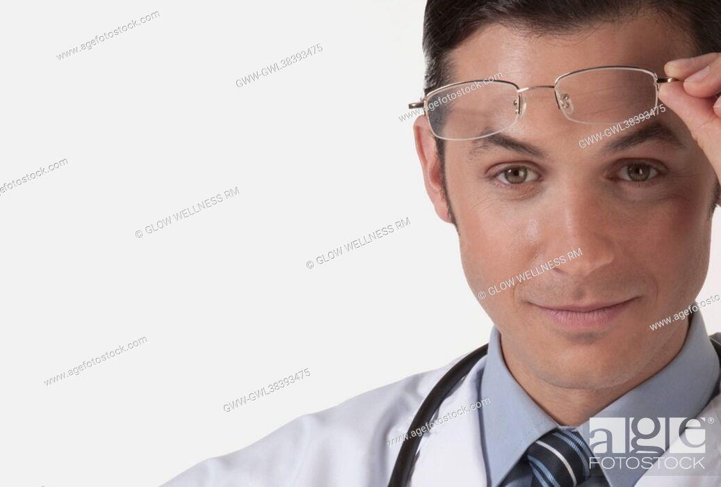 Imagen: Portrait of a doctor holding eyeglasses.