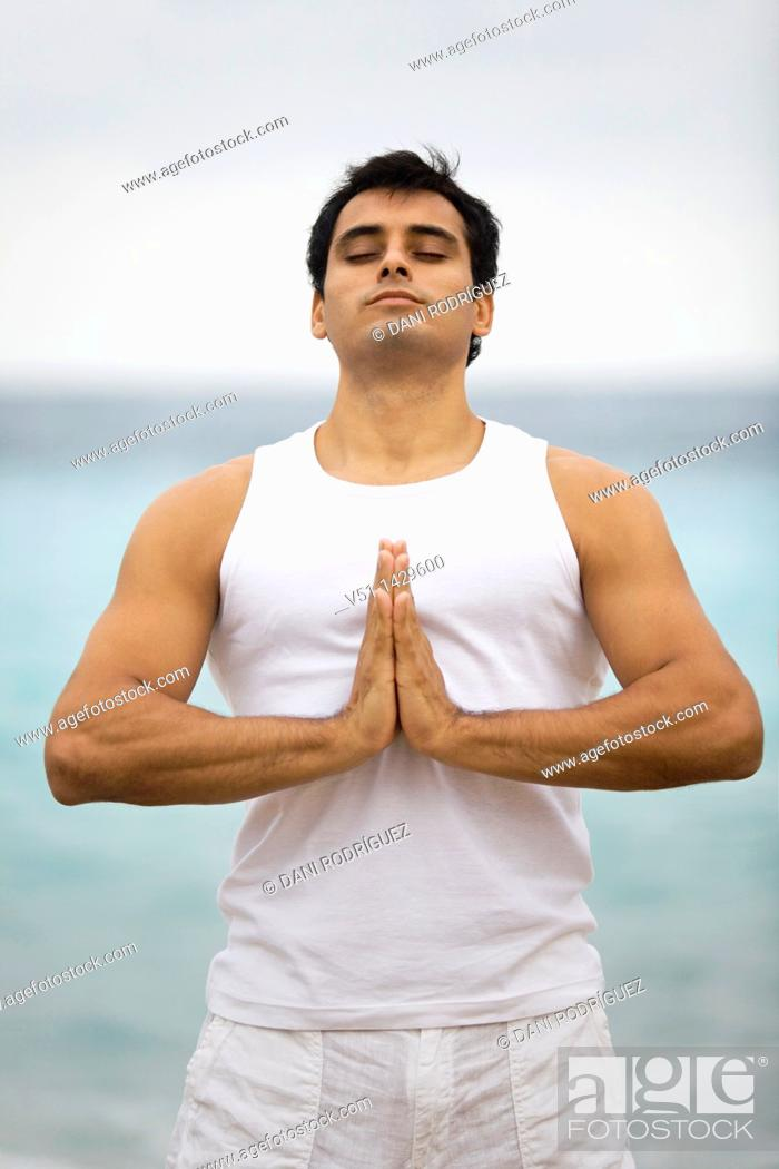 Stock Photo: Young man doing yoga at the beach.