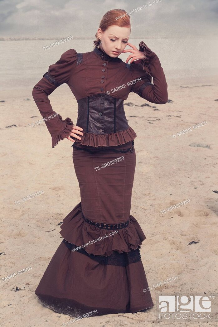 Stock Photo: Young woman in a victorian dress standing alone outdoors beside the sea.