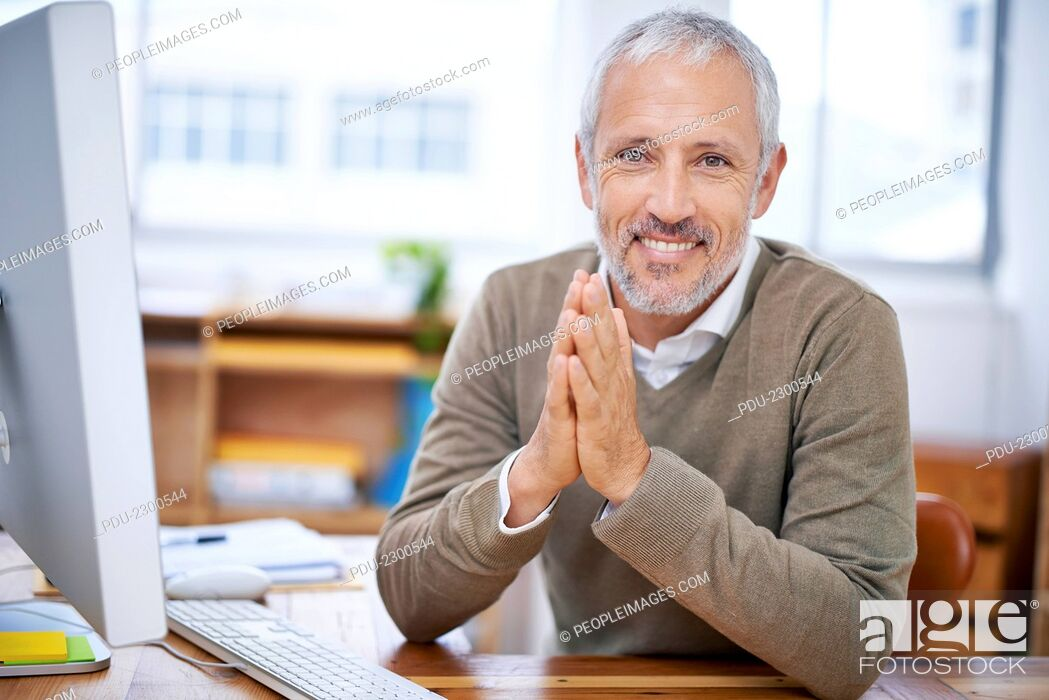 Stock Photo: A portrait of a happy businessman sitting at his desk at work.