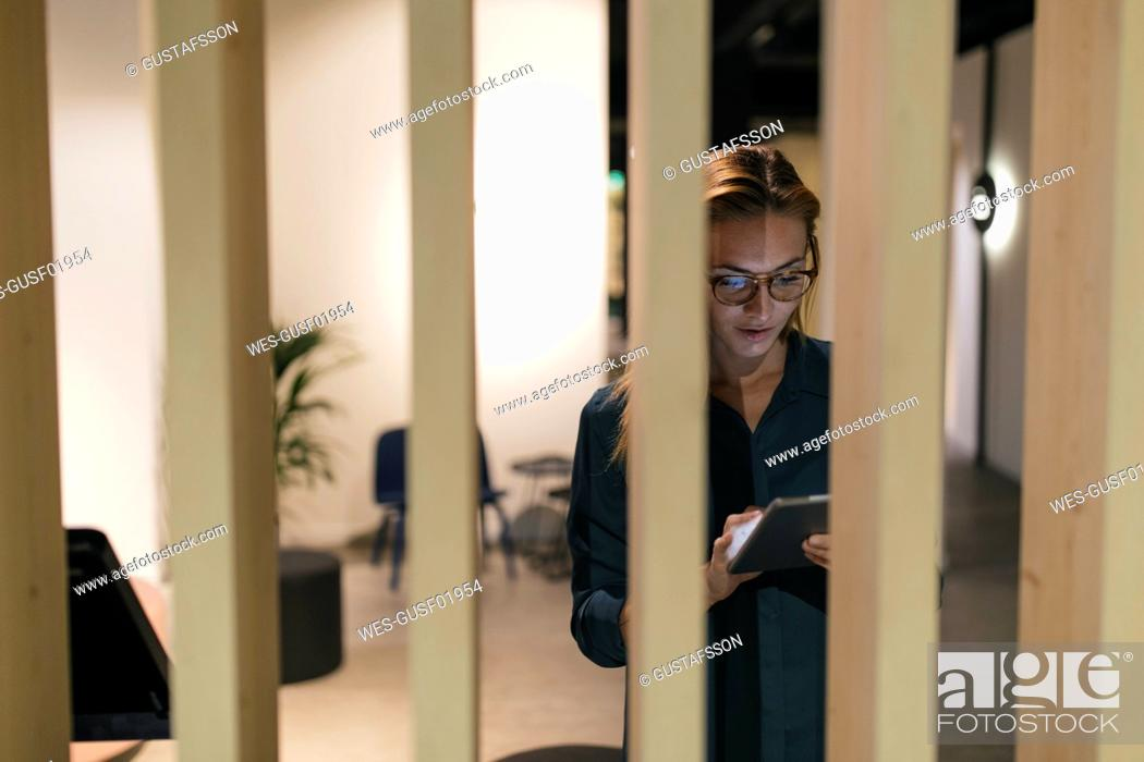 Stock Photo: Businesswoman using tablet in modern office.