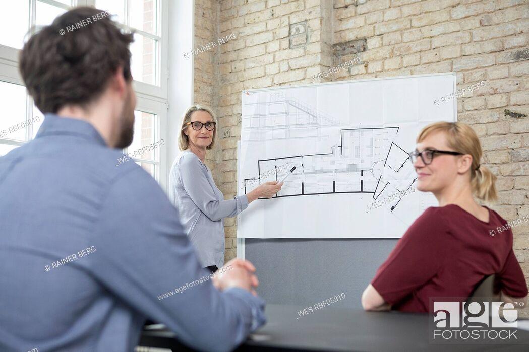 Stock Photo: Mature businesswoman explaining floor plan to colleagues.