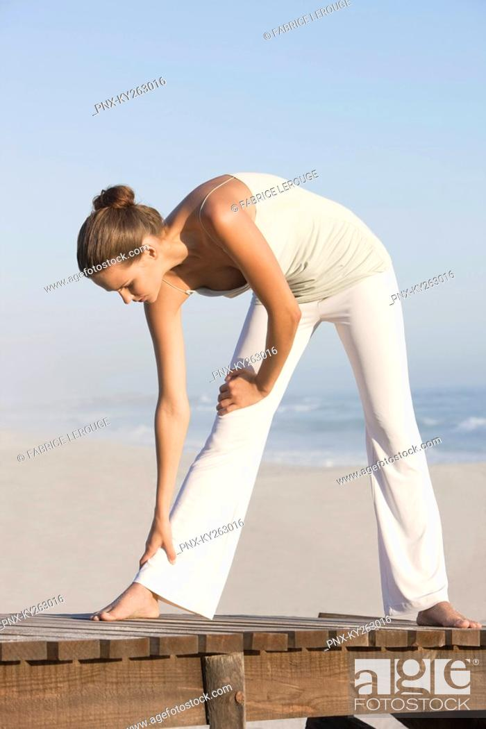 Stock Photo: Woman stretching on a boardwalk.
