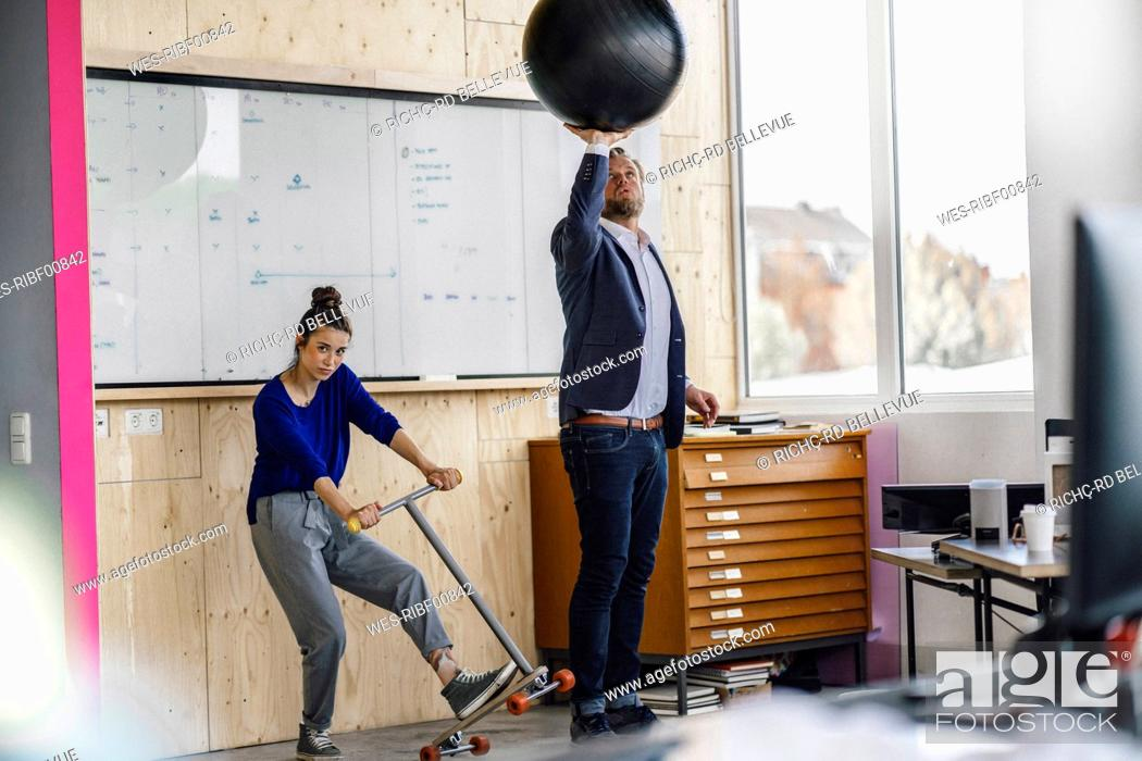 Stock Photo: Mature man and his assistent playing with scooter, standing in office in front of white board.