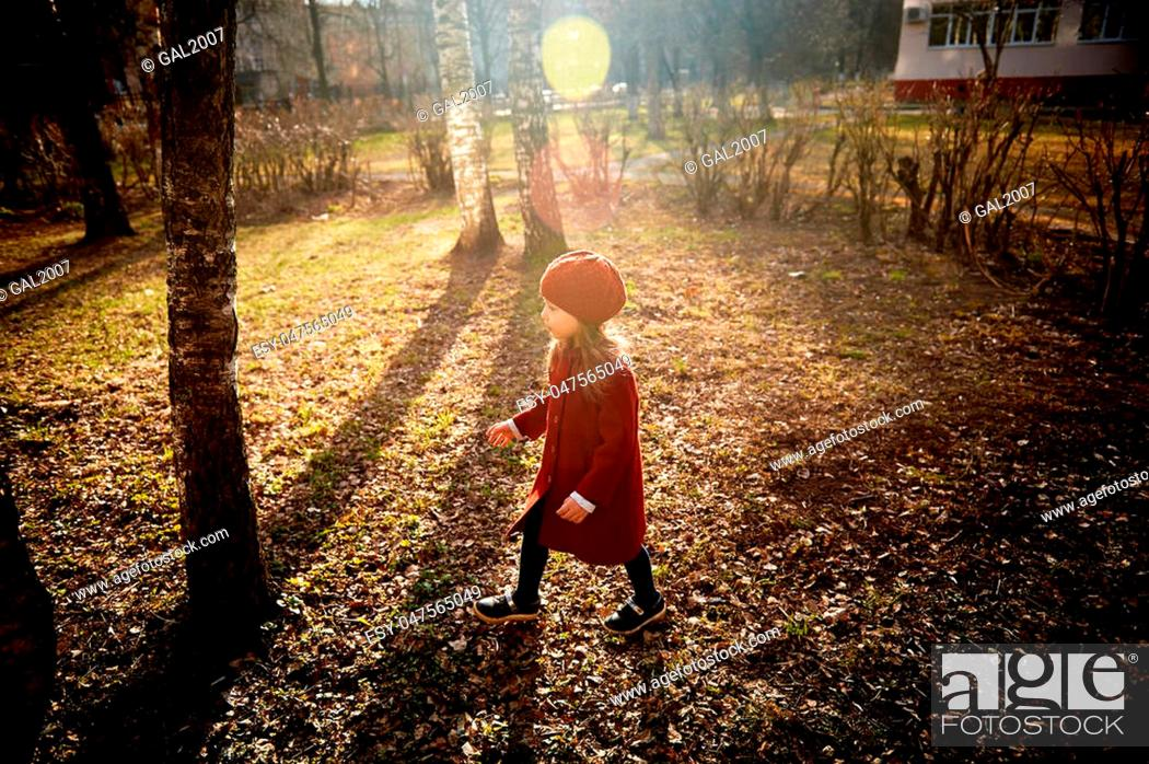 Stock Photo: Baby 3 years with long hair. In a red beret and coat spinning in the street , in the rays of the sun. The state of happiness. Childhood.
