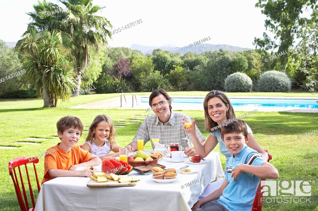 Stock Photo: Family with three children 6-11 sitting at table in garden portrait.