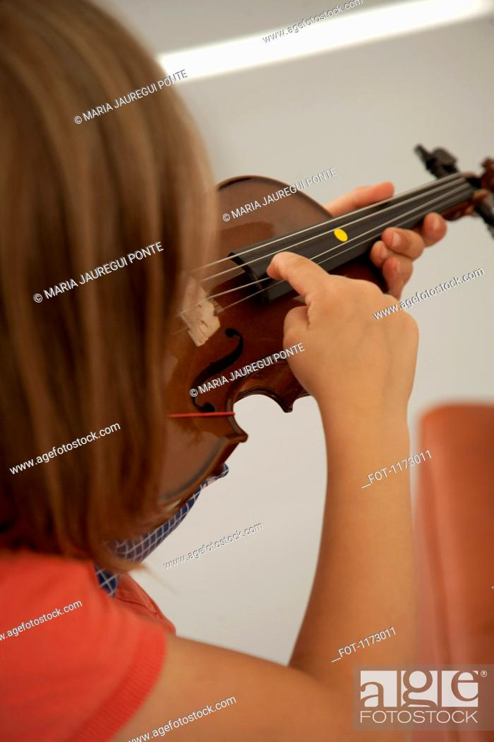Stock Photo: Girl plucking the string of a violin.