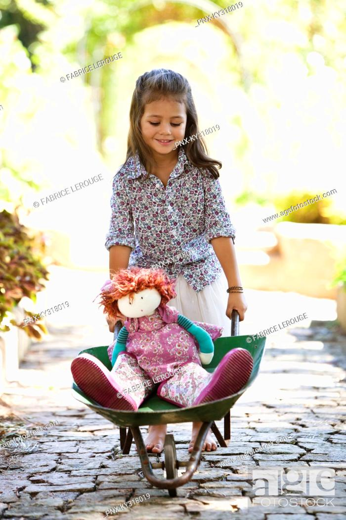 Stock Photo: Cute girl pushing a wheelbarrow filled with toys.