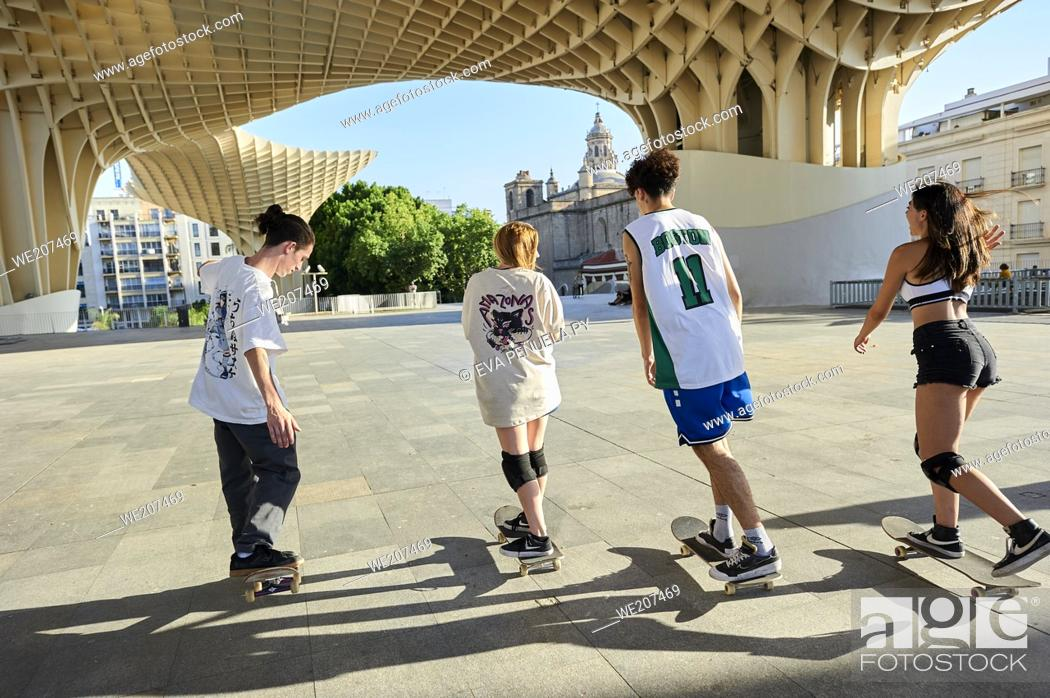 Stock Photo: Group of young people riding on skateboard in the city.