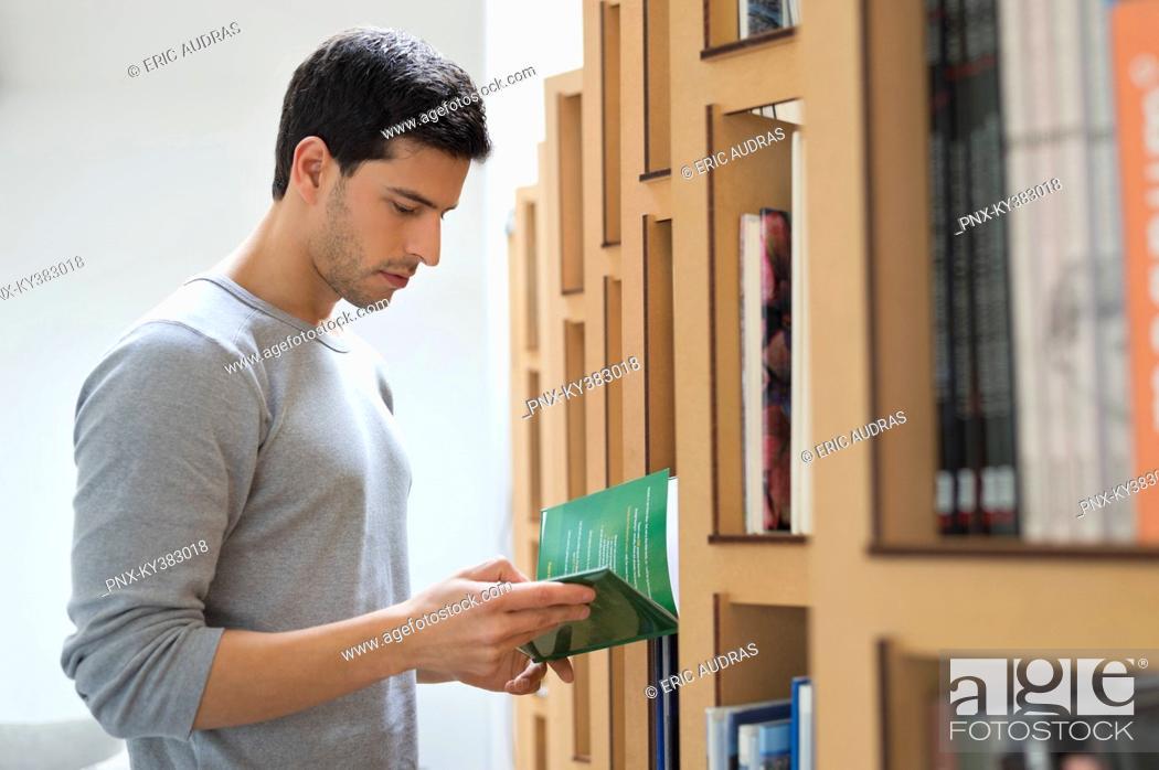 Stock Photo: Man choosing a book from a bookshelf.