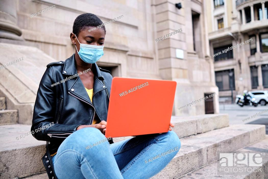 Imagen: Young woman wearing protective face mask using laptop while sitting on steps in city.