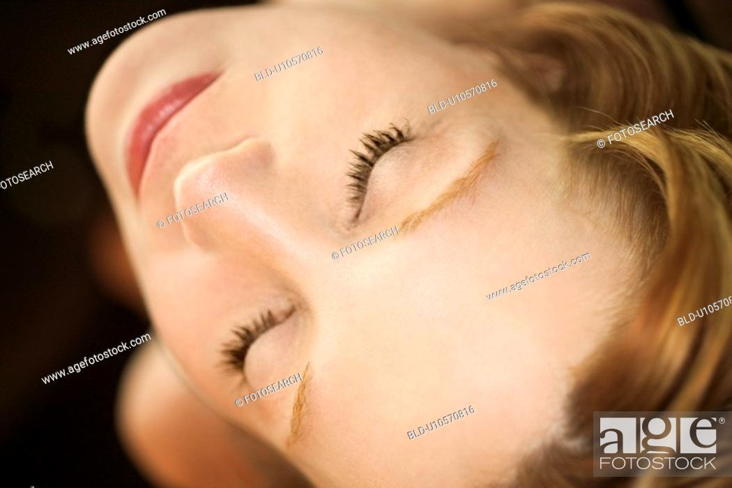 Stock Photo: Close up portrait of pretty redhead woman with eyes closed.