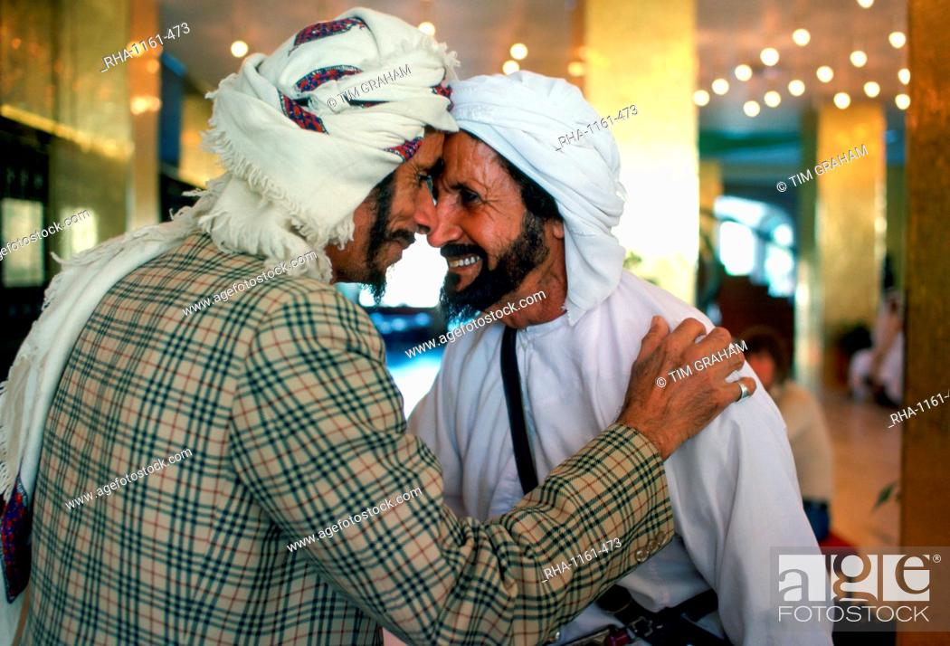 Two men wearing arab headdresses giving the traditional arab stock photo two men wearing arab headdresses giving the traditional arab greeting in the hilton m4hsunfo