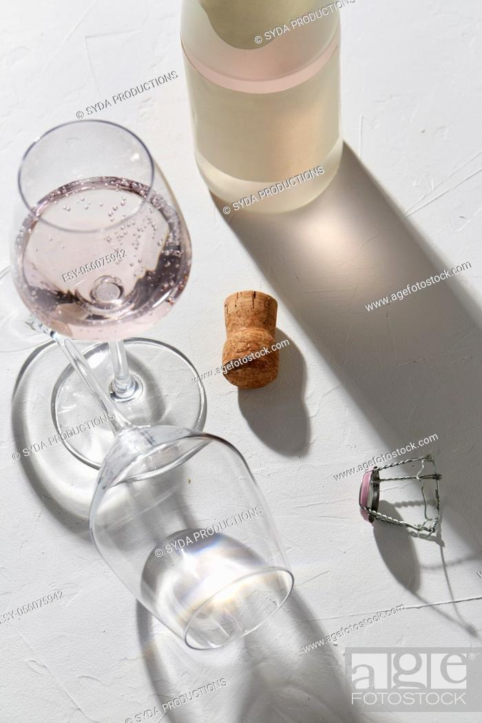 Stock Photo: wine glasses and champagne bottle dropping shadows.