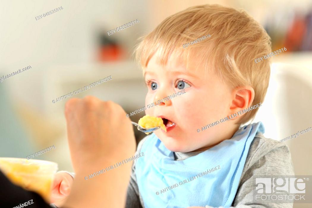 Stock Photo: Close up portrait of a mother hand feeding a baby at home.
