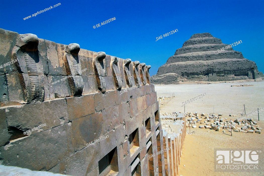Stock Photo: Cobra frieze, detail of the defensive wall of the Pyramid of Djoser, with the pyramid in the background, Saqqara Necropolis, Memphis (Unesco World Heritage List.