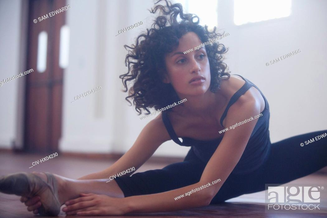 Stock Photo: Focused young female dancer stretching leg in dance studio.