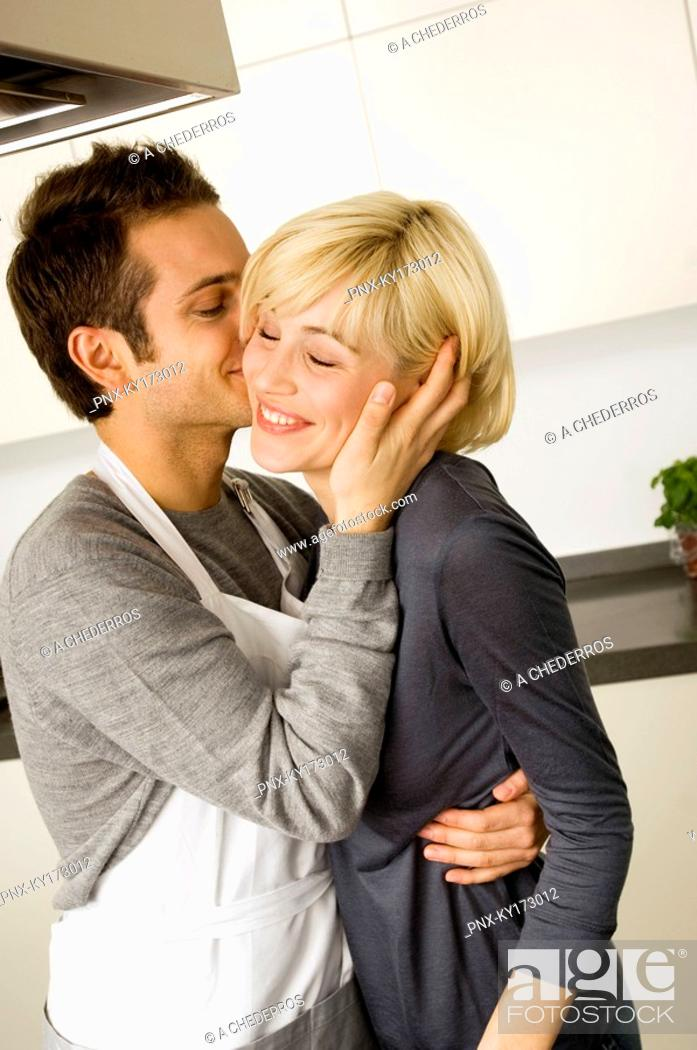 Stock Photo: Side profile of a young man kissing a young woman in the kitchen.