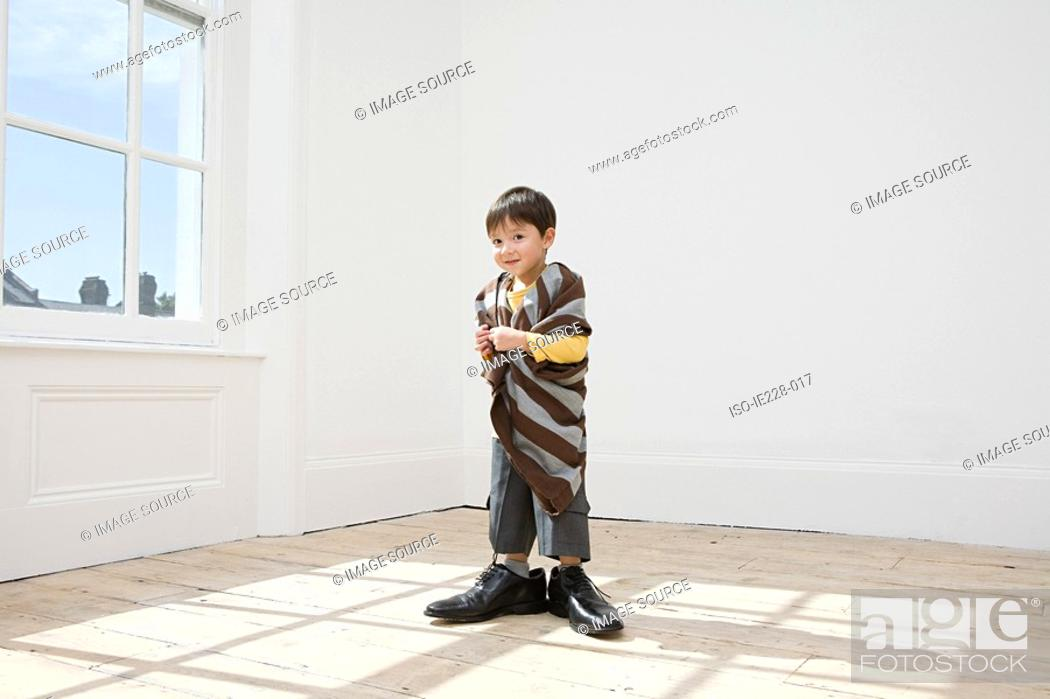 Stock Photo: Boy dressing up in large clothes.