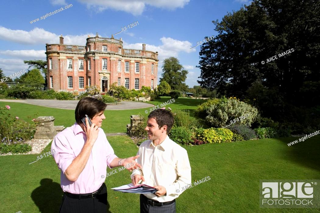 Stock Photo: Man using mobile phone smiling at man with paperwork in grounds by manor house, elevated view.