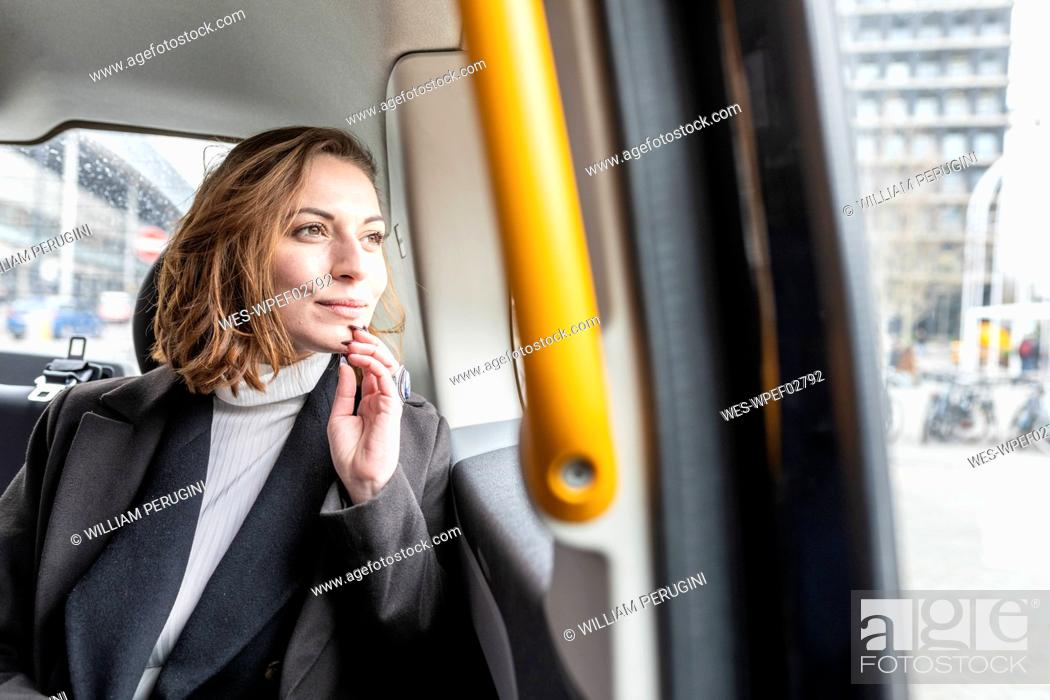 Stock Photo: Woman in the rear of a taxi looking out of the window, London, UK.