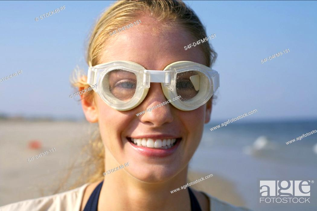 Stock Photo: Young woman with diving goggles at the beach, selective focus.