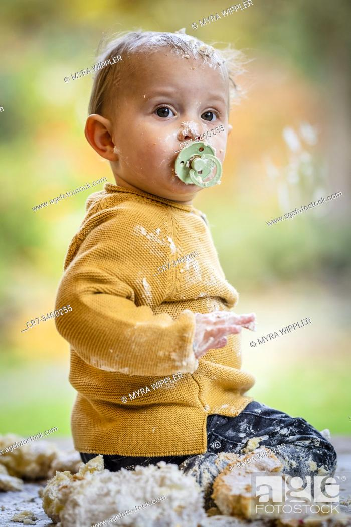 Stock Photo: Baby boy having fun on his one year birthday, smashing a birthday cake.