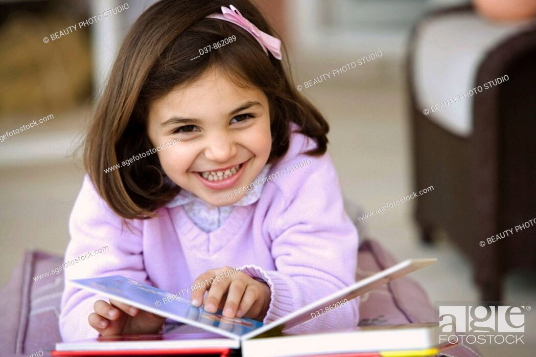 Stock Photo: Little girl reading a book.